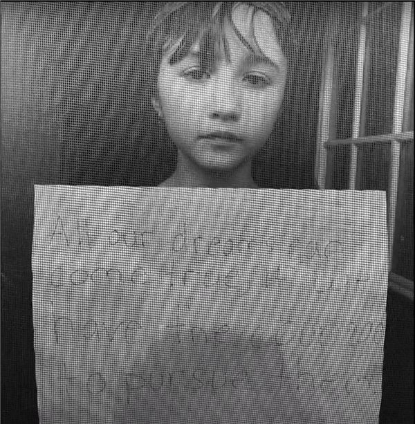 fourth grader holding sign through a window